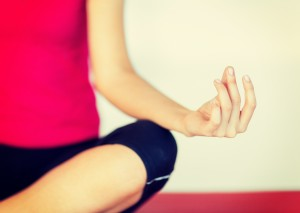 sport and yoga concept - girl sitting in lotus position and meditating